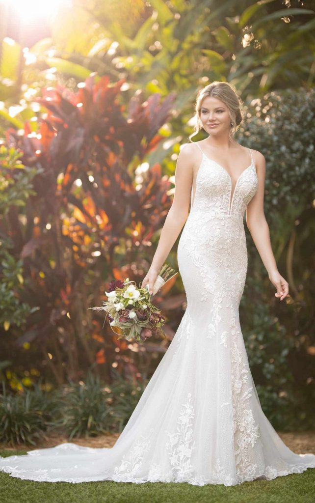 SPARKLING FIT-AND-FLARE WEDDING DRESS WITH SIDE CUTOUTS This gown was made to help show off your natural shine on your big day. A sultry silhouette smooths over the curves gracefully with a plunging V-neckline and whisper-thin straps, bedecked in gorgeous beading for a dazzling effect. The deep side cutouts mirror the neckline and open V-back, while a combination of glitter tulle and honeycomb tulle creates a mix of textural shine throughout the lacy silhouette. Organically placed laces along the hem create a uniquely scalloped train for the grand finale.