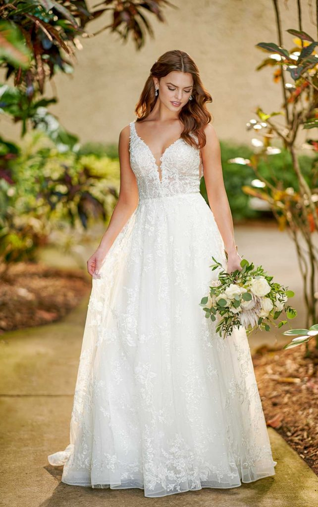 RELAXED A-LINE WEDDING DRESS WITH LACE Casual princess brides, this one is for you. This soft A-line style has a little bit of everything, while staying subtle enough to let you do the shining. The V-neckline features a skinny plunge for coverage, while wider lace straps offer support and comfort. Beadwork is concentrated throughout the neckline to highlight the upper body just so, while a sequin layer is added to the flowing skirt to add a hint of shine and dimension with your every move. Organically placed laces are featured throughout the skirt to enhance the flowing movement of this gown, while an open V-back features subtle organic finishing for an added natural touch.